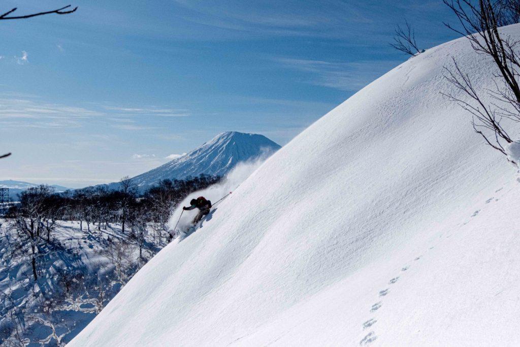 skier enjoying well deserved turns in the niseko backcountry